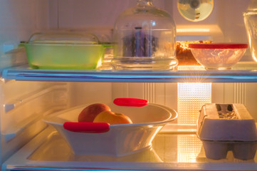 Front view of an open refrigerator full of fresh food