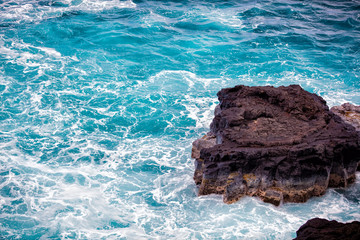 Wall Mural - rock with blue water and splashing waves