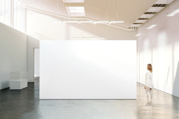 Woman walking near blank white wall mockup in modern gallery. Girl admires a clear big stand mock up in museum with contemporary art exhibitions. Large hall interior, banner exposition show Fototapete