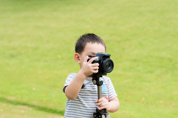 Asian baby boy taking photo graphy in nature by DSLR camera and tripods