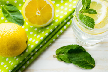 Homemade lemonade with lemons and mint on wooden table