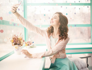 Vintage toned photo of young beautiful pretty woman making selfie in a cafe. Trendy pink and blue colors.