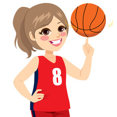 Active teenager girl spinning basketball with finger