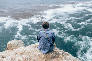 A young adventurous man sitting on the top of the cliff overlooking the pacific ocean