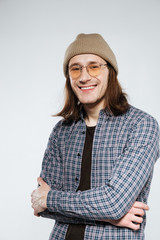 Vertical image of Smiling hipster in eyeglasses with crossed arms