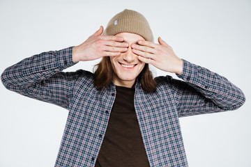 Smiling hipster covering his eye