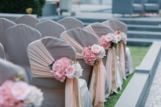 Wedding chairs decorated with bouquets of flowers