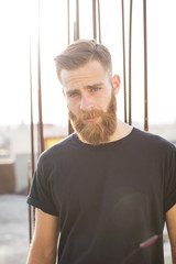 Bearded man posing in the street.