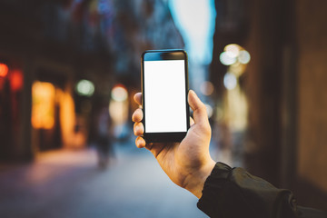 Mock-up of blank screen of smartphone, male hand holding modern black cellphone with template screen with area for your logo or design, evening city street in the background