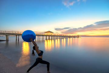 Silhouette yoga ball, pilates ball young woman in the beach sunset background,wooden bridge laying to the sea at sunset