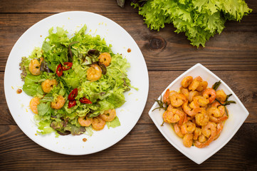 Salad with fried shrimps. Wooden background. Top view. Close-up