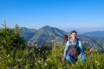 Sporty woman, traveler with backpack relax on the alpine meadow