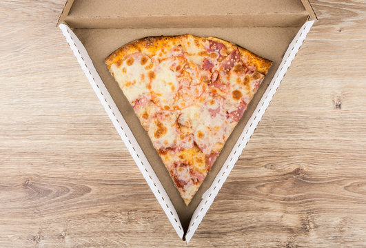 Piece of pizza in carton box on wooden table