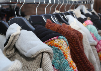 stall with many vintage clothes and used sweaters hanging