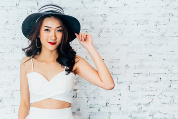 Young happy Asian woman smiling in fashionable dress and summer hat over white brick wall