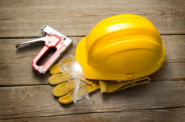 Yellow hard hat with protective glasses and stapler on wooden background