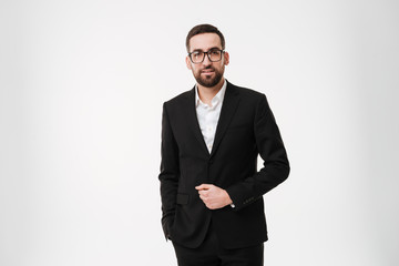 Concentrated young bearded businessman wearing glasses