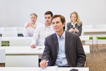 Business people in a seminar listening to a spreech