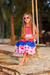 Cute little girl on a swing. A child plays outdoors in summer.