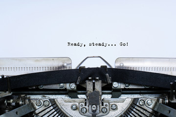 ready. steady. go. slogan taped words on a vintage typewriter