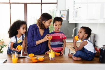 Une mère et ses trois enfants préparent du jus d'orange dans la cuisine