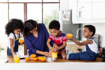 Une famille prépare du jus d'orange dans la cuisine