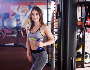 Sporty woman with shaker of protein in hand, standing in gym