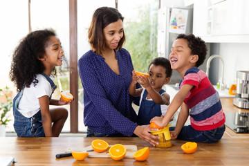 famille qui s'amuse en préparant du jus d'orange dans la cuisine