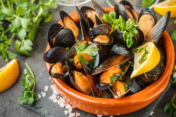 Foto op Plexiglas Schaaldieren Mussels in wine with parsley and lemon. Seafood. Clams in the shells. Delicious snack for gourmands. Selective focus