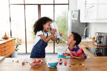 Une petite fille verse de la chantilly dans la bouche de son petit frère