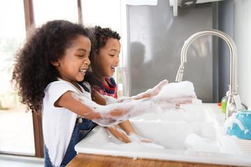 Un garçon et une fille font la vaisselle dans la cuisine