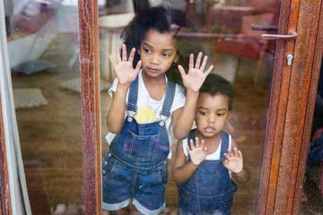 Une petite fille et un bébé regardent dehors par la fenêtre