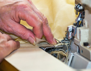 Hands of a woman who works on the sewing machine