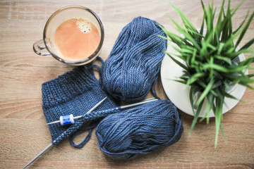 Green plant in the pot, knitting needles, blue yarn, and black coffee are on the table. Wooden...