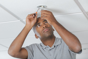 electrician fitting lightbulb in office