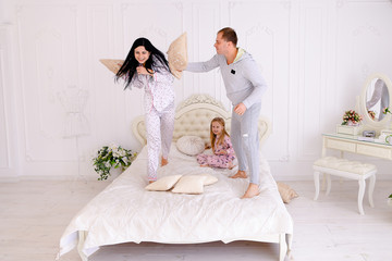 Portrait of family jumping on bed looking at camera together in
