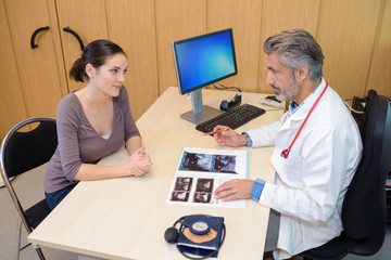 Doctor looking at scan images with patient