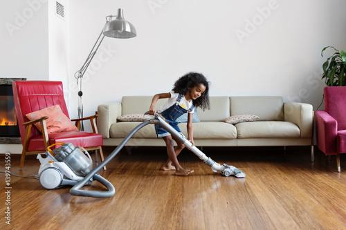 une petite fille passe l 39 aspirateur dans le salon en. Black Bedroom Furniture Sets. Home Design Ideas