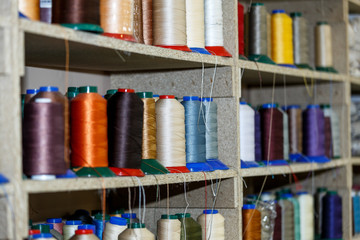 Spools of thread which are on the shelves and the loom