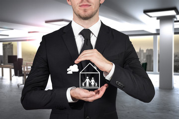businessman protecting papercut family home with hands