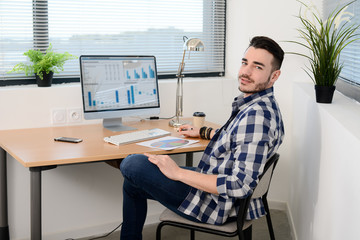 portrait of a young man in casual wear working in creative business startup company office with computer