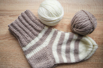 Beige and white yarn, beige-beige sock are on the table. Wooden background. Hobbies