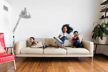 Trois enfants jouent avec des coussins sur le canapé du salon