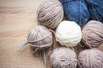 Knitting needles, beige, white and blue yarn are on the table. Wooden background. Hobbies