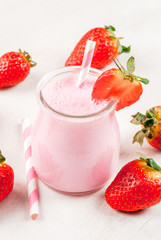 Summer dessert or breakfast - strawberry milkshake with mint, in a small jar, with a striped tube. On a white table. copy space