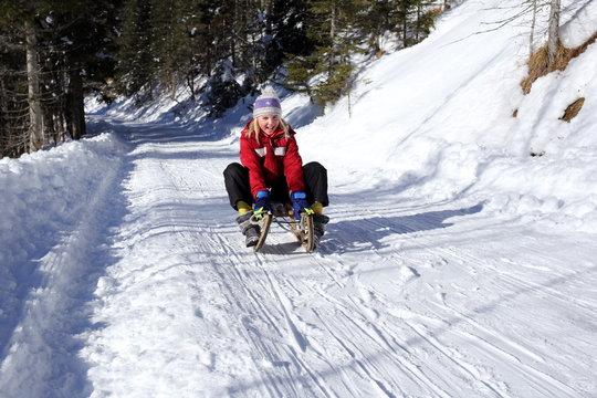 Mädchen beim Rodeln im Winter