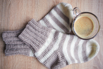 Striped beige-white knitted socks and the black coffee. Wooden background. Knitting hobby