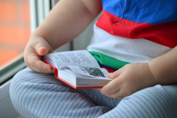 Baby boy reading a book, dclose up of hands Leafing through the pages
