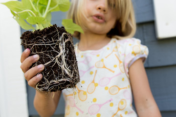 Girl holding sweet potato vine with exposed roots