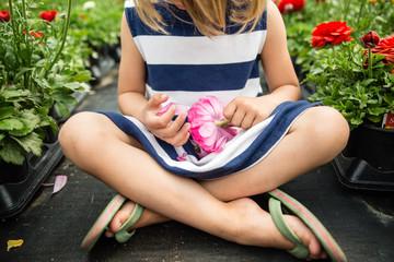 Girl sitting crossed legged holding ranunculus flower